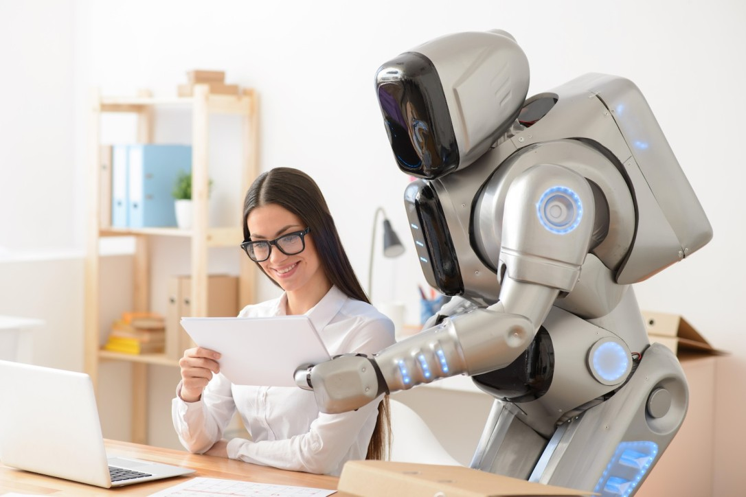 Pleasant girl and robot working in the office