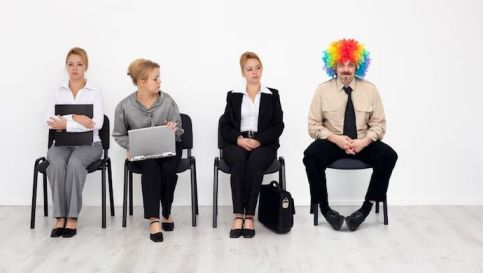 16229690 - there's one in every crowd - clown among job candidates waiting