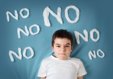 52382205 - bad boy on blue blanket background. angry child with no words around