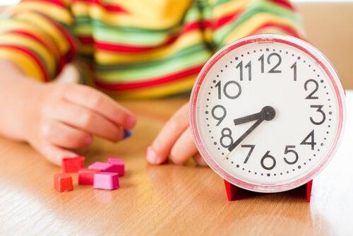 Niño-jugando-con-piezas-pequeñas-y-un-reloj